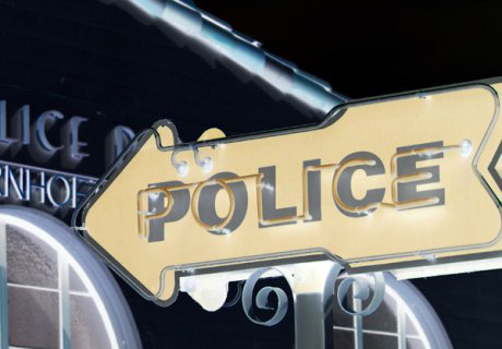 police-sign-with-building-crop-small-inverse